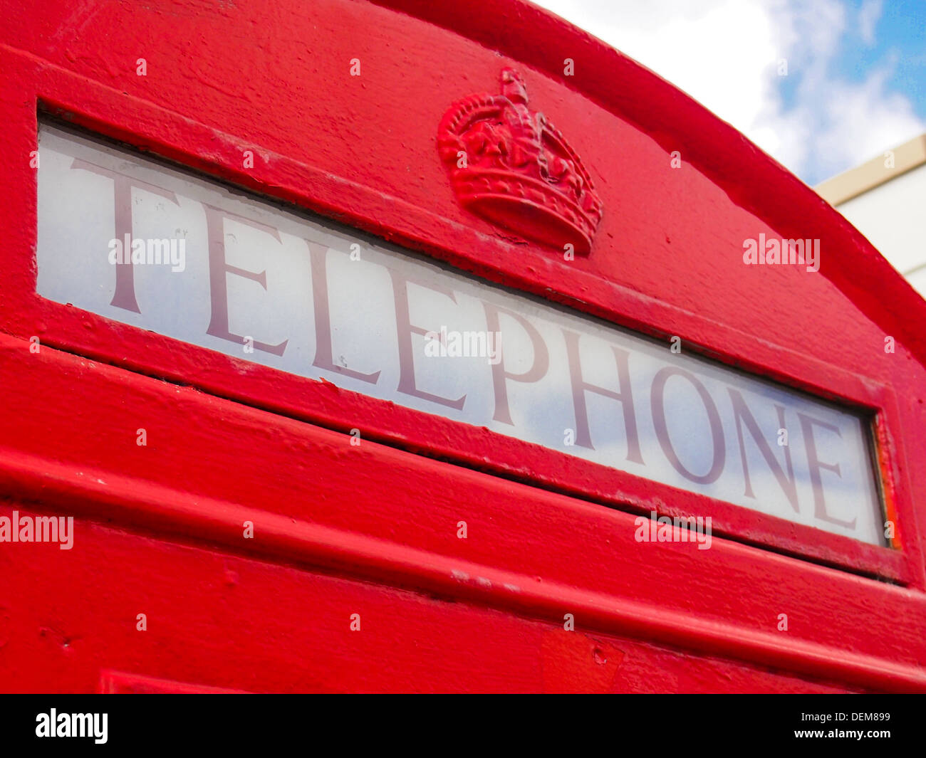 Detail of the top of an old British red telephone box design K6 showing the Telephone sign and Crown. - Stock Image