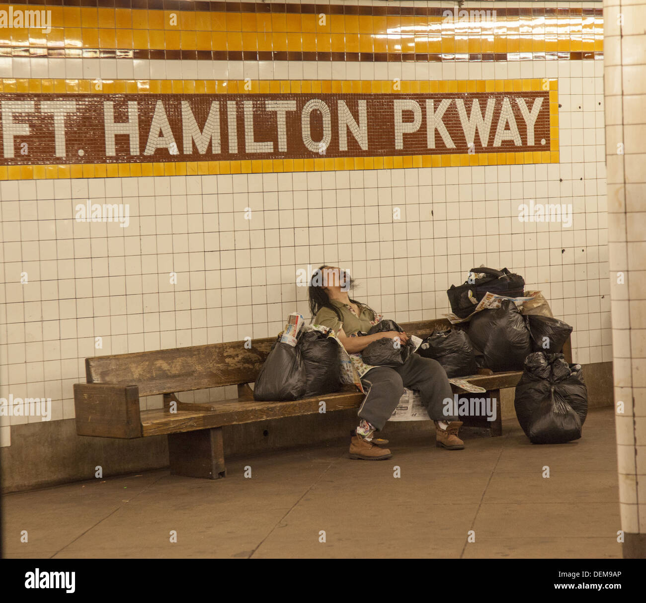 Homeless man with his possessions on the platform at a subway station in Brooklyn, NY. - Stock Image