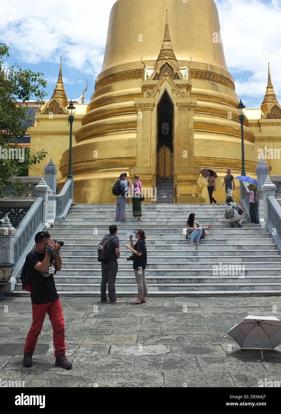 Tourists take photos at the golden Phra Si Rattana Chedi at the Grand Palace complex in Bangkok Stock Photo
