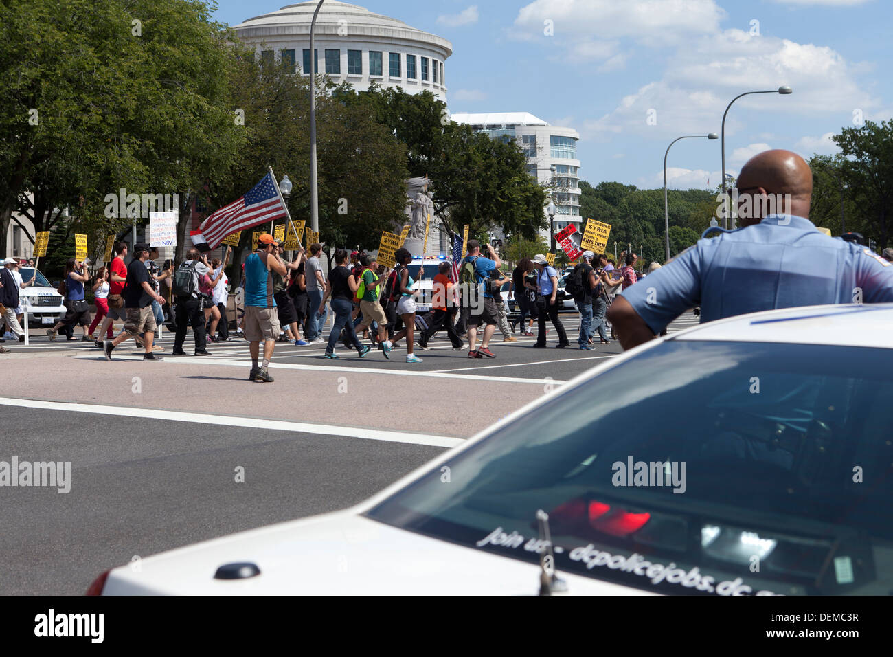 Policeman watching demonstrators - Washington, DC USA - Stock Image
