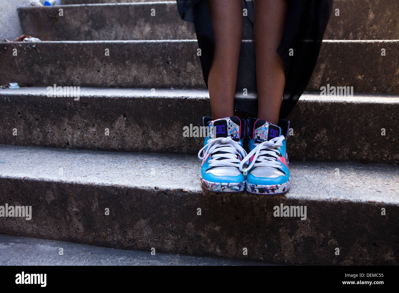 Closeup of girl wearing DG sneakers, standing on stairs - Stock Image
