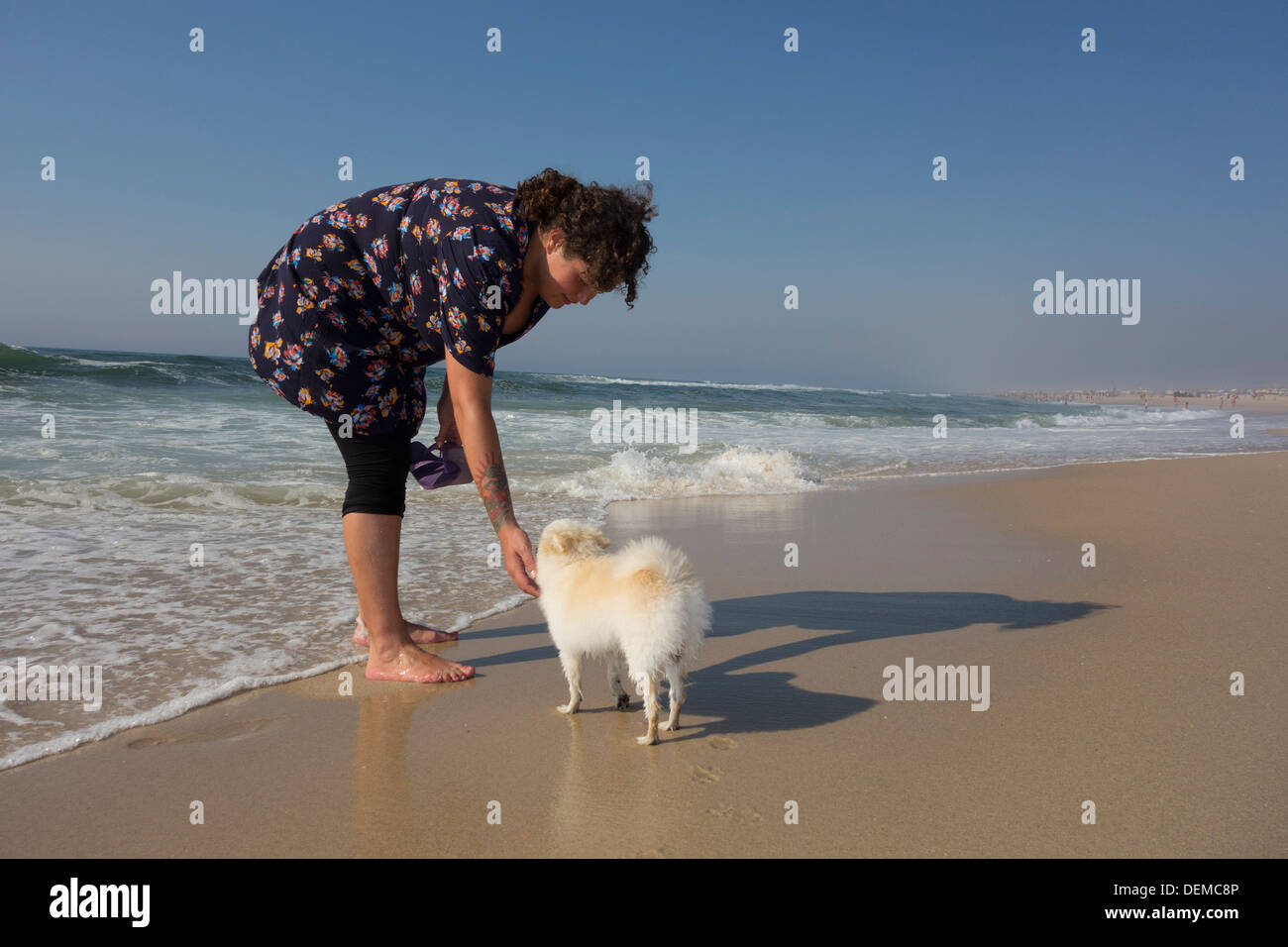 Young Woman With Small White Pomeranian Dog On The Beach Stock Photo