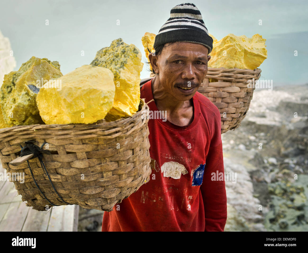 Portrait of a sulfur miner carrying baskets loaded with sulfur at Kawah Ijen volcano in East Java, Indonesia. - Stock Image