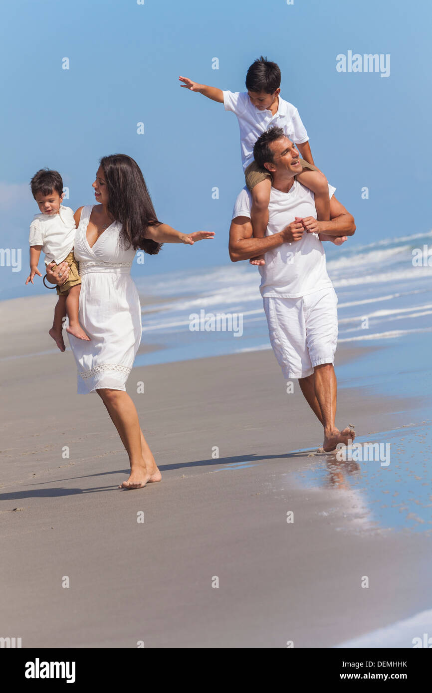 A happy family of mother, father parents & two boy son children, playing and having fun in the waves of a sunny beach - Stock Image