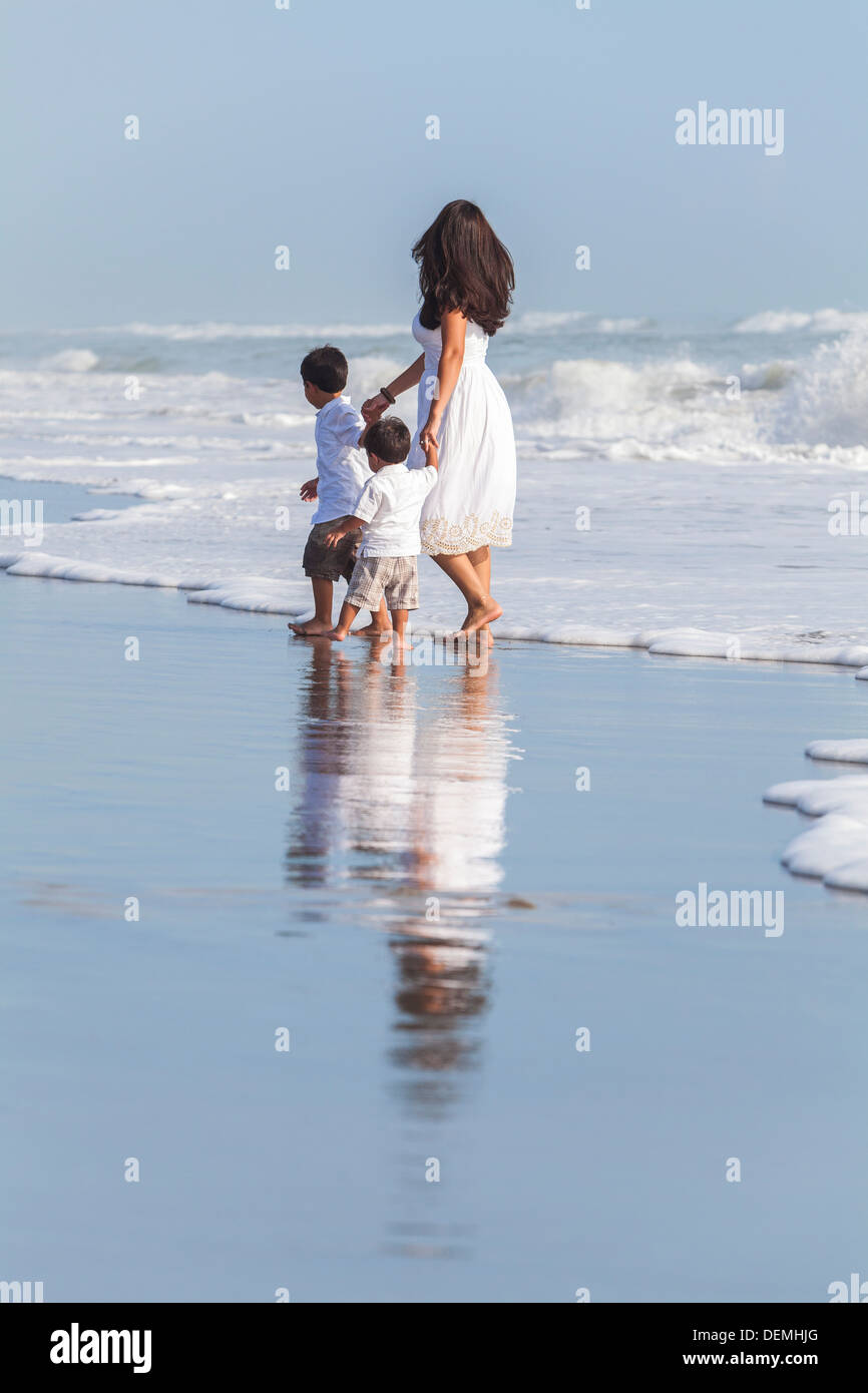 A family of single mother and two boy children sons holding hands in the waves of a sunny beach - Stock Image