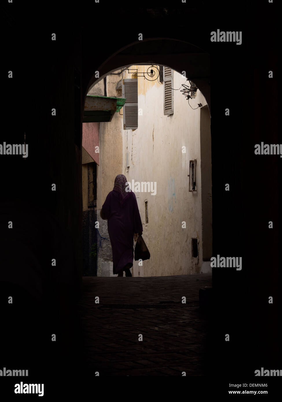 Silhouette of arab woman with hijab walking through a dark alley in Tangier, Morocco - Stock Image