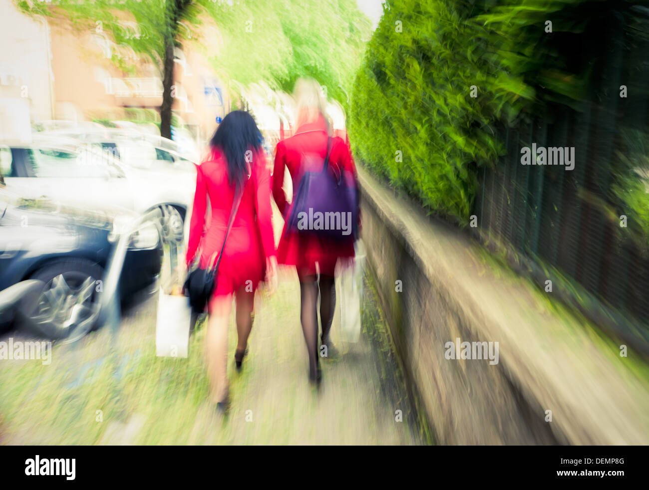 Two unrecognizable fashionable women in red going ahead, intentional motion blur - Stock Image