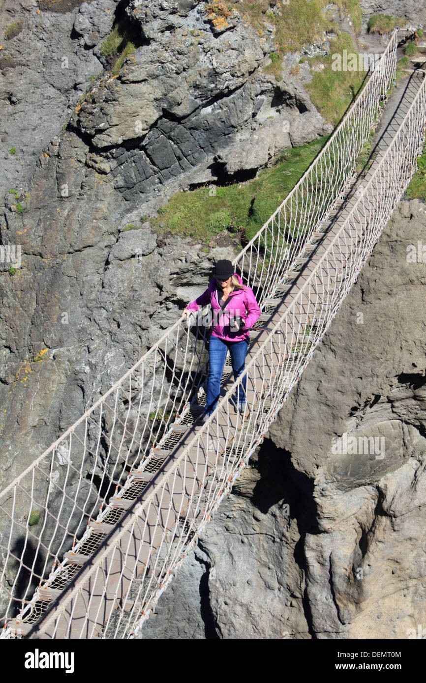 Woman crossing Carrick-a-Rede, rope bridge on the Causeway Coastal Route, Northern Ireland. - Stock Image