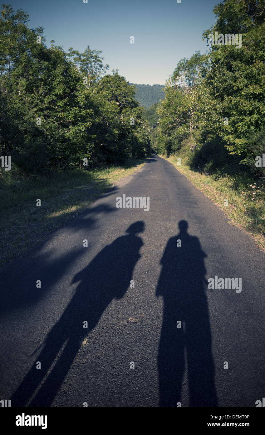 Shadows of couple walking down a country lane in France on the GR65 walking route, the Way of Saint James, Camino de Santiago - Stock Image