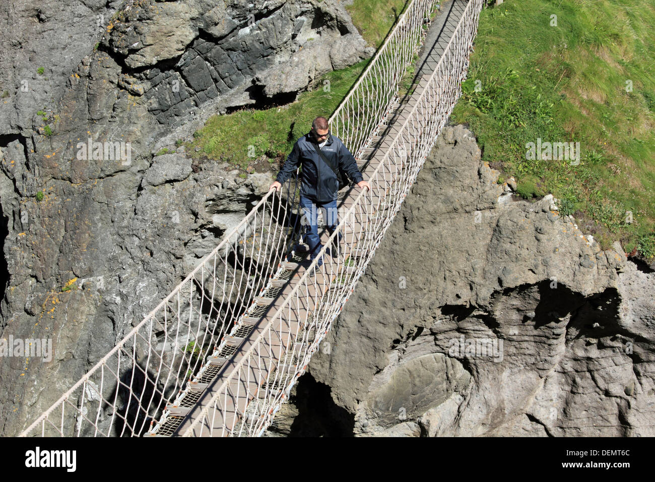 Man crossing Carrick-a-Rede rope bridge on the Causeway Coastal Route, Northern Ireland. - Stock Image