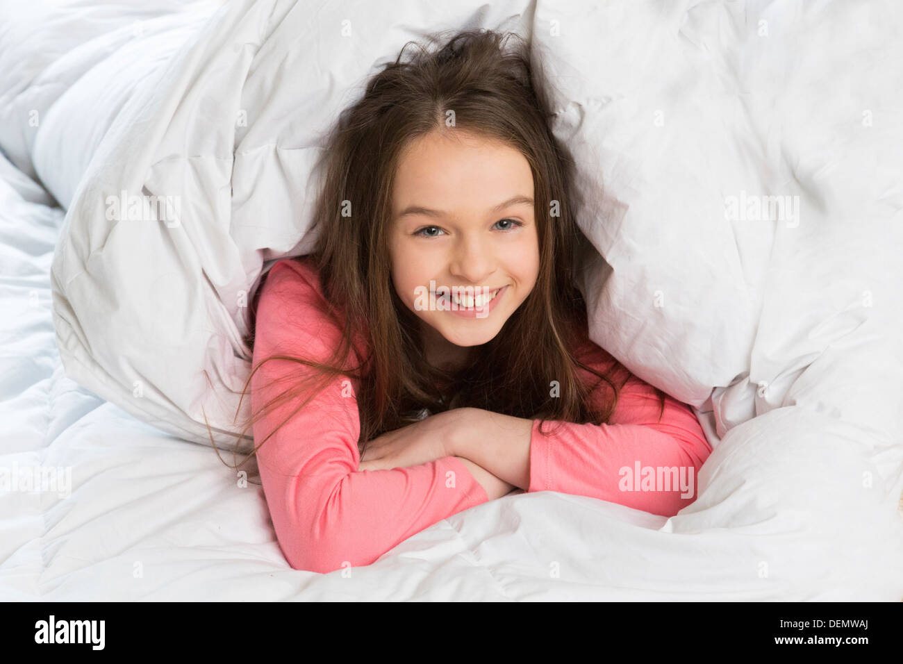 young girl in bed upbeat and smiling Stock Photo