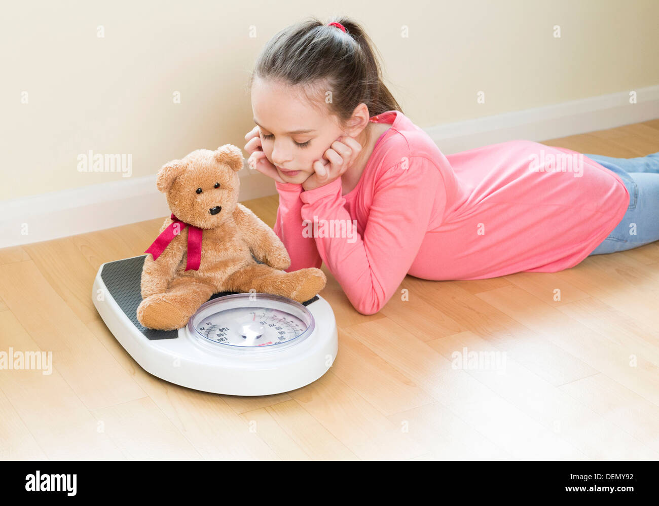 young girl weighing her teddy bear Stock Photo