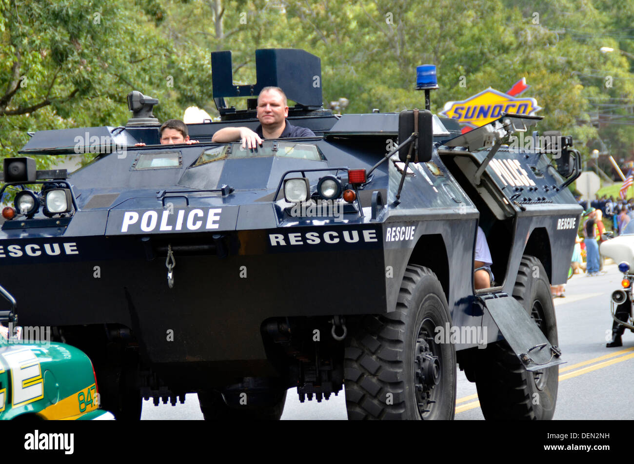 Policeman driving an armored personnel carrier with his children riding inside during a parade in Greenbelt, Maryland - Stock Image