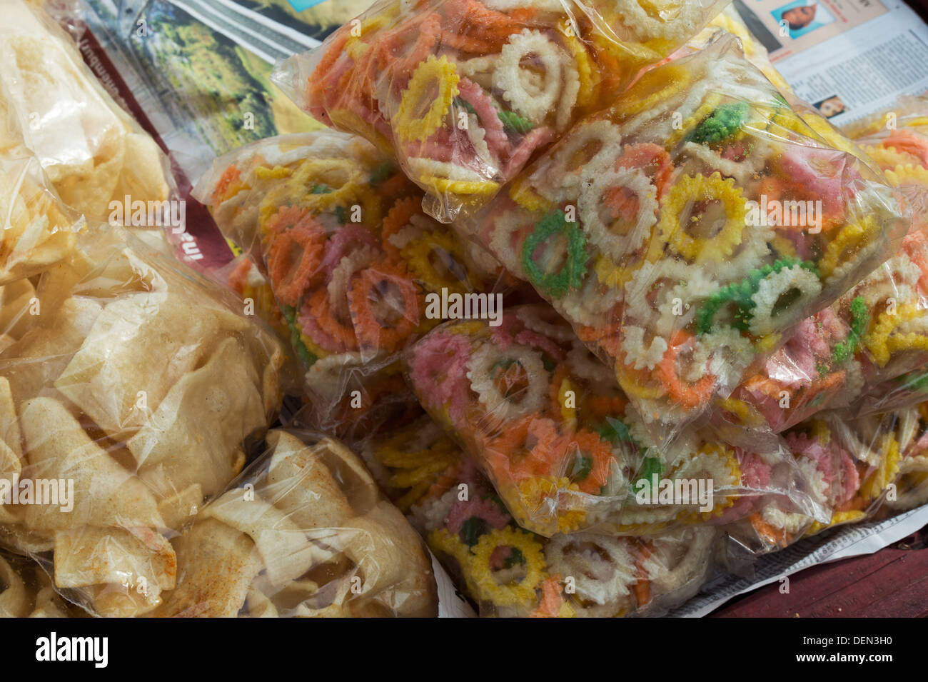 Deep fried indian snacks in plastic bags for sale at an indian market. India - Stock Image