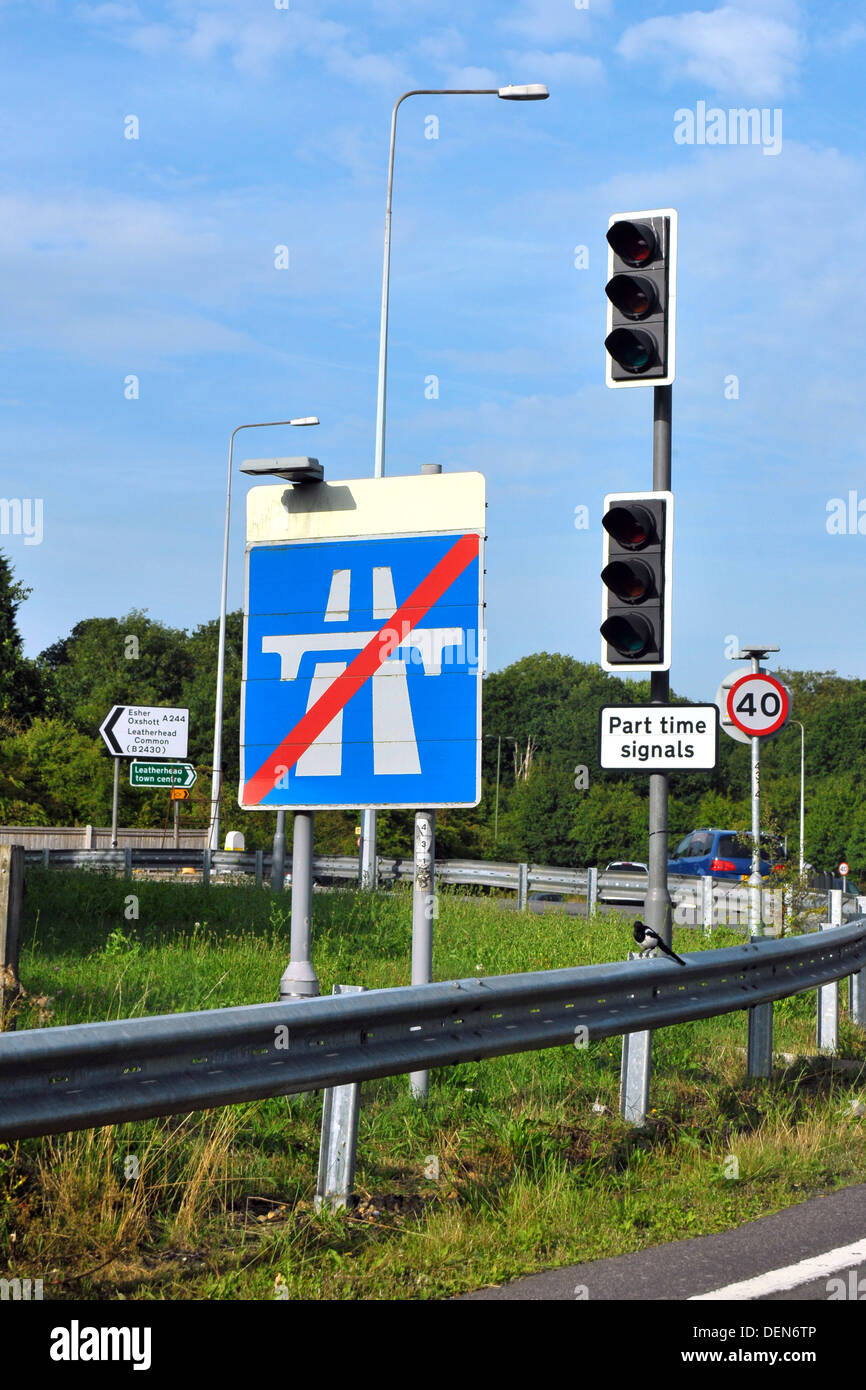 A British road sign indicating the end of the motorway next to traffic lights. Stock Photo