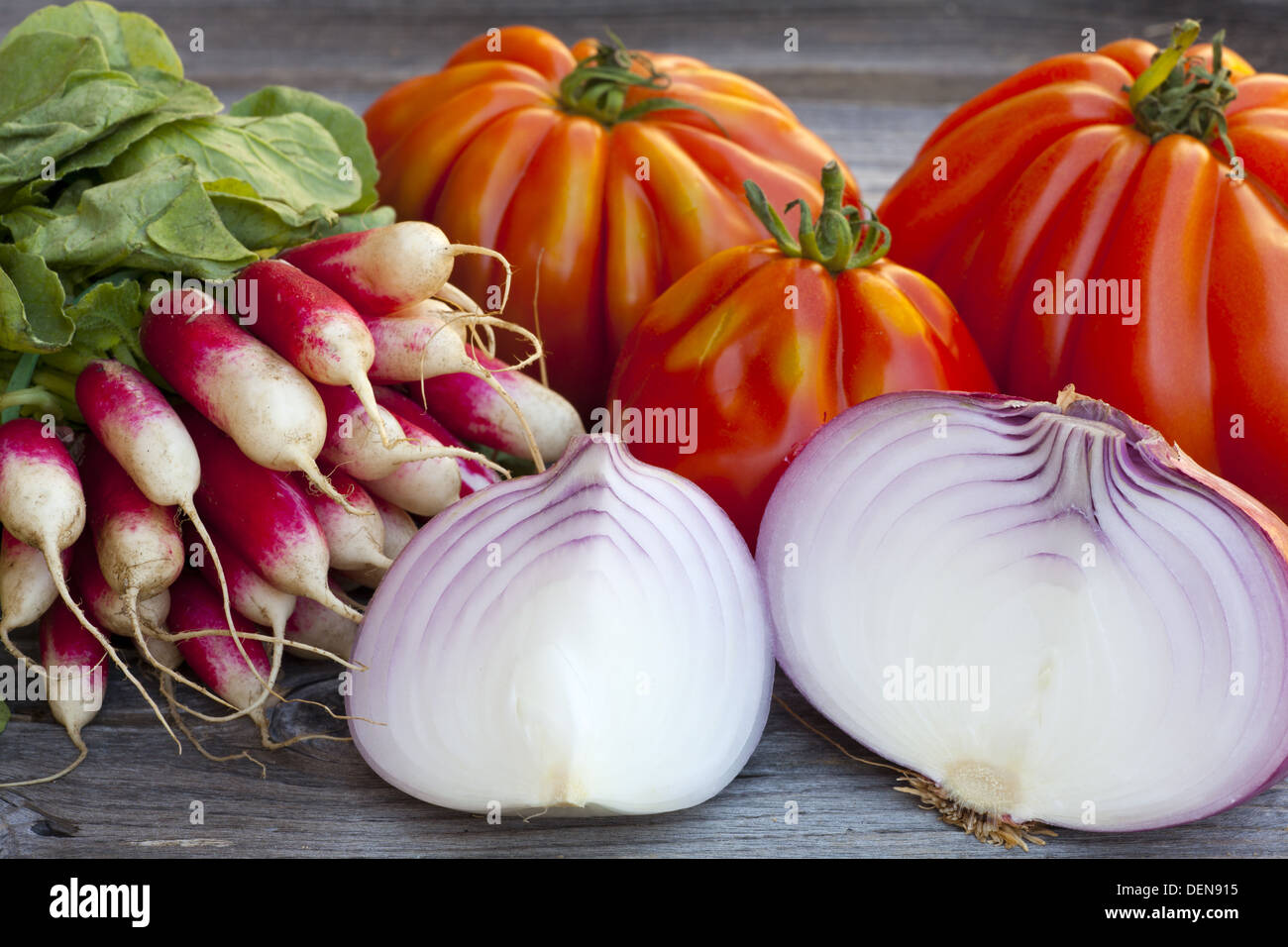 Coeur de Boeuf Tomatoes, large red Onions and Radishes fresh from the Weekly Market on a old wooden Table - Stock Image