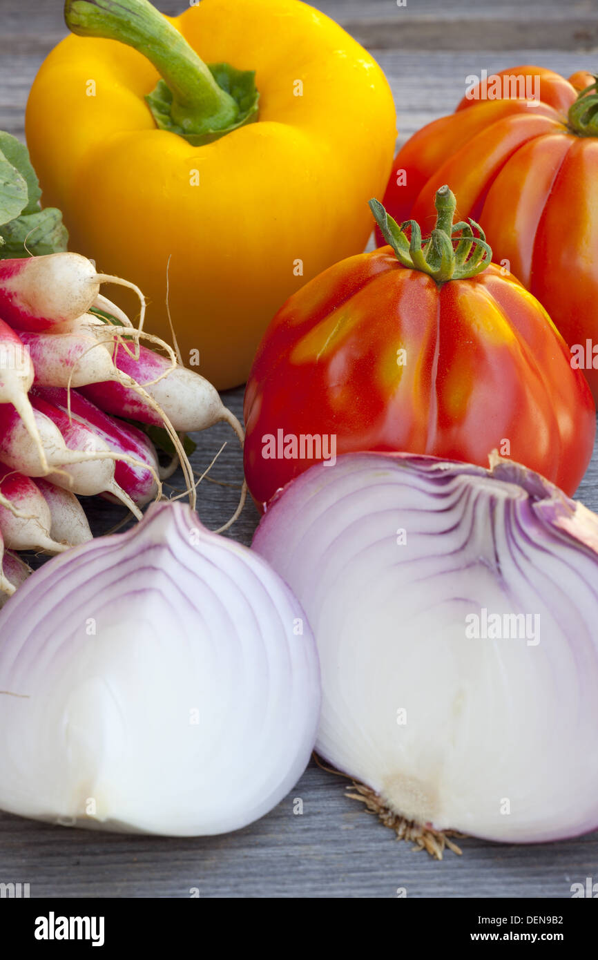 Fresh vegetables with Tomatoes, Red Onions, Radishes and Paprika from the Weekly Market on a old wooden Table - Stock Image