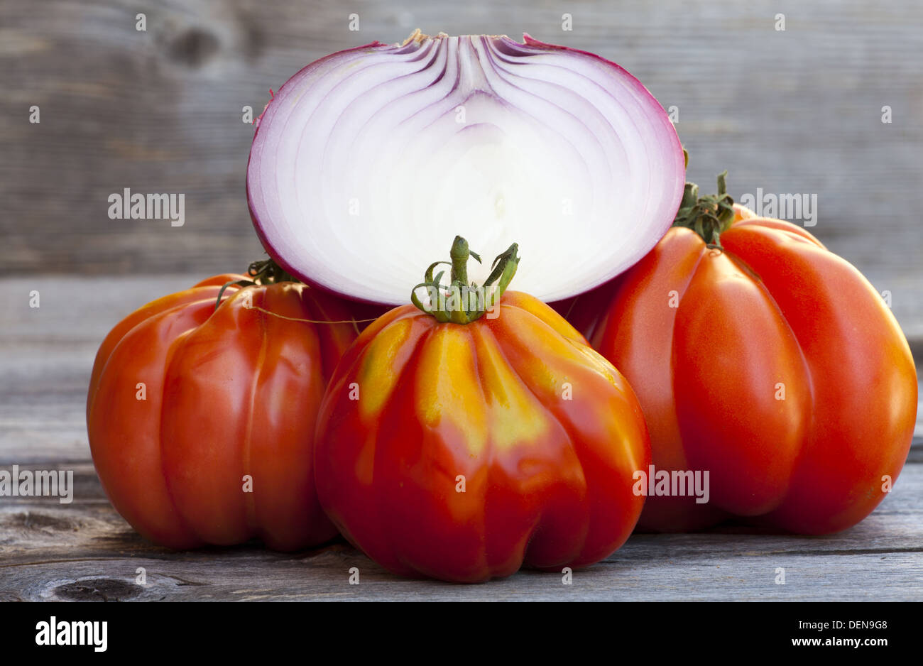 Three Oxheart Tomato and a halved red Onion from Weekly Market in South France on a old wooden Table - Stock Image