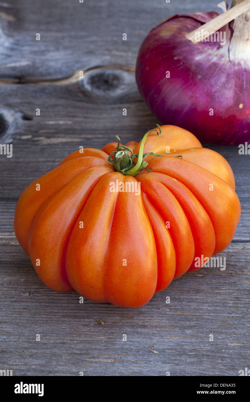 One Beefsteak Tomato and a whole red Onion from Weekly Market in South France on a old wooden Table - Stock Image