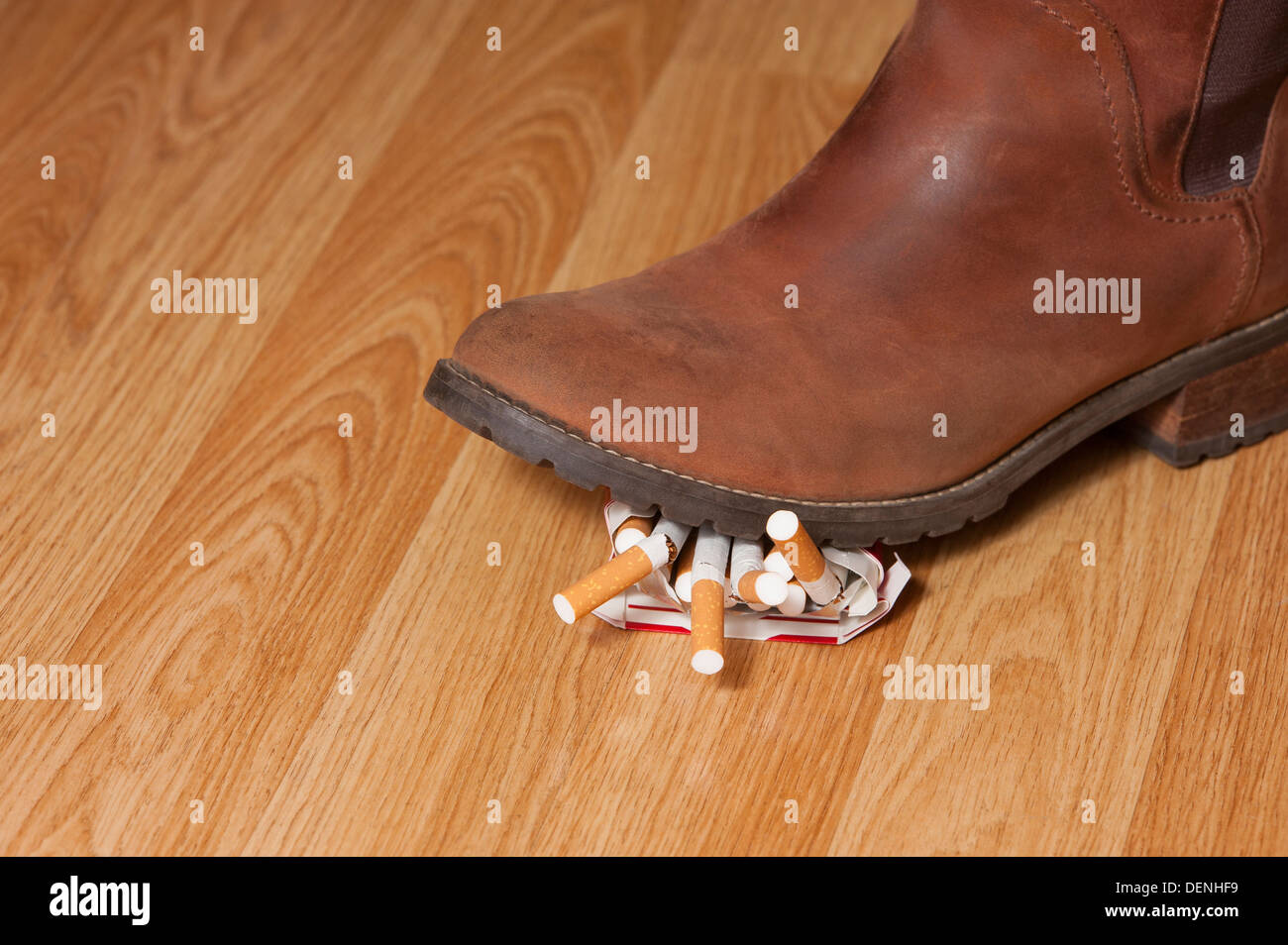 A leather boot shown squashing a packet of cigarettes whilst getting ready to give giving up smoking  for stoptober . - Stock Image