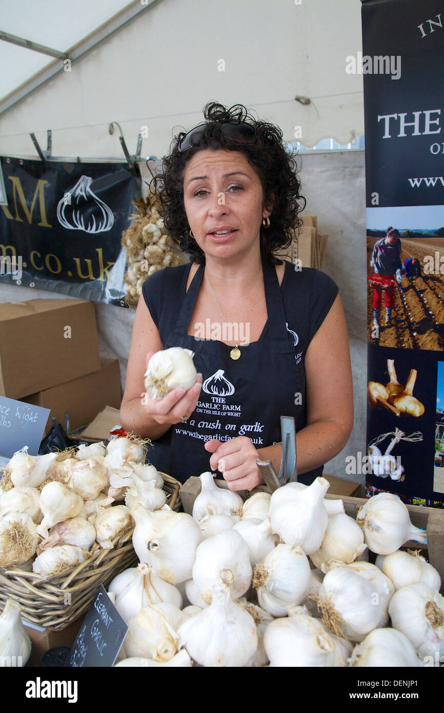 Stall holder with elephant garlic at Abergavenny Food Festival 2013 - Stock Image