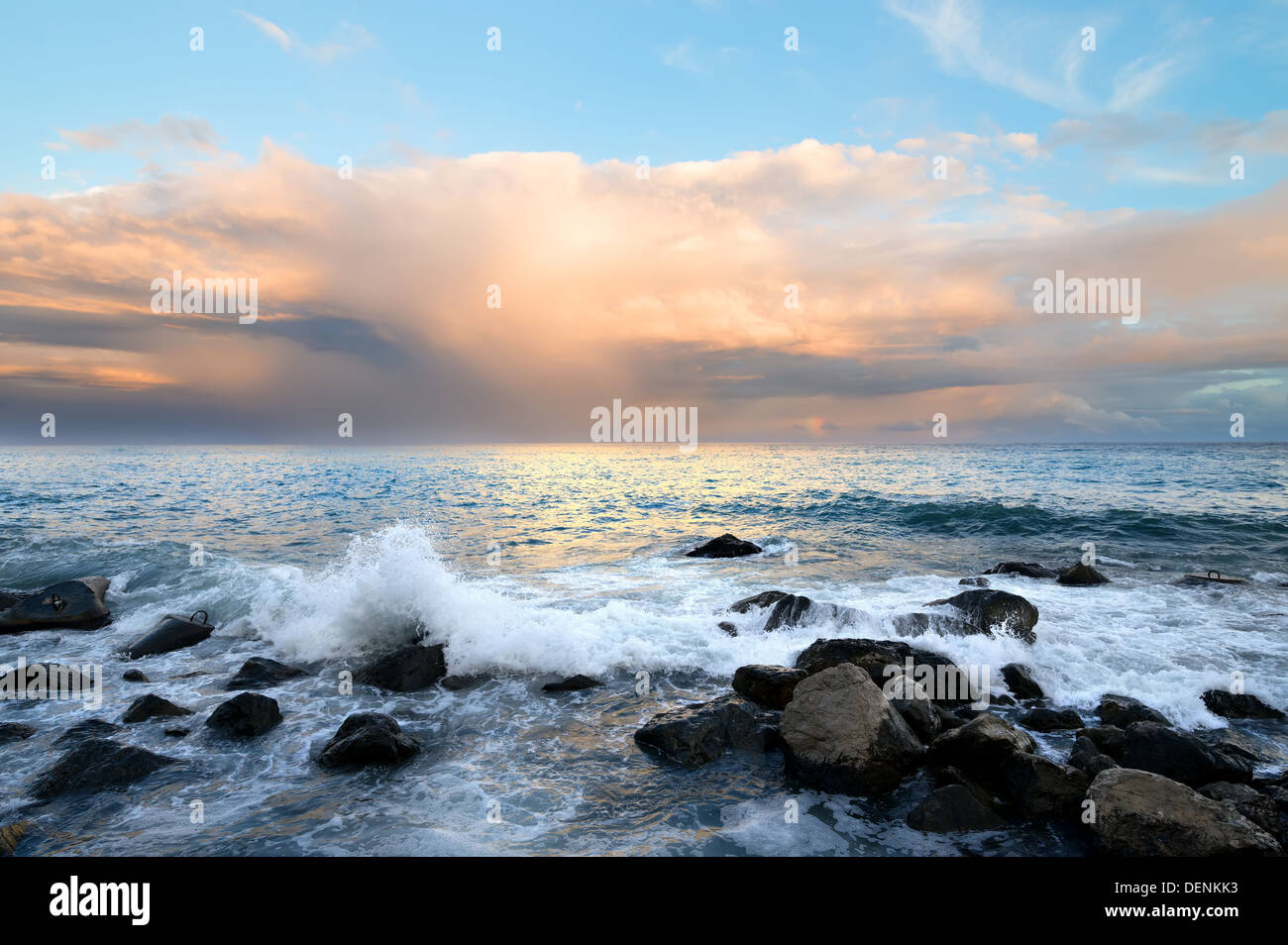 Rocky coast and sea waves at sunset - Stock Image