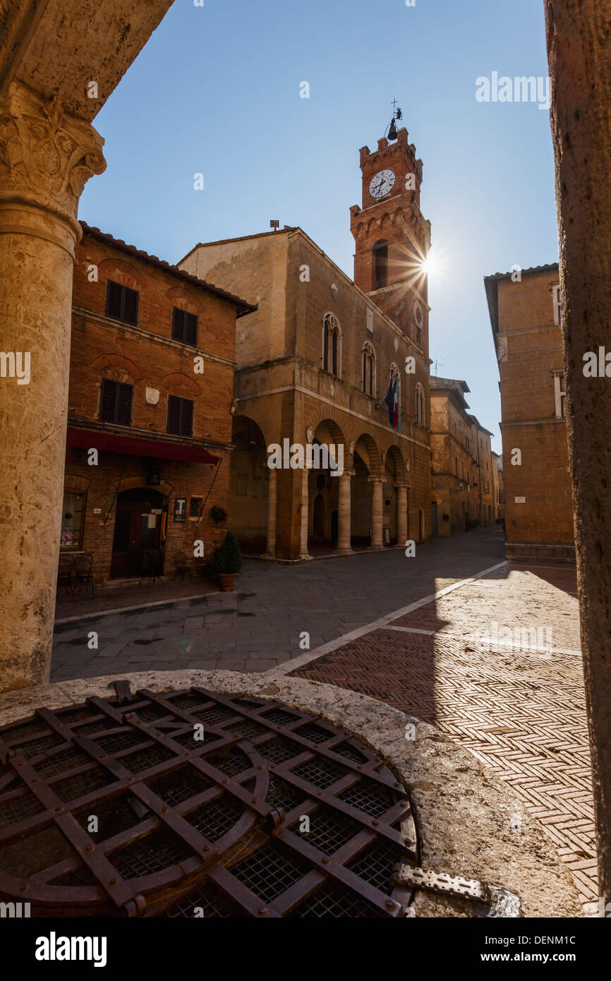 Piazza Pio II and the Palazzo Comunale (Comunal Palace) at sunrise viewed through the ancient well, Pienza, Tuscany. - Stock Image