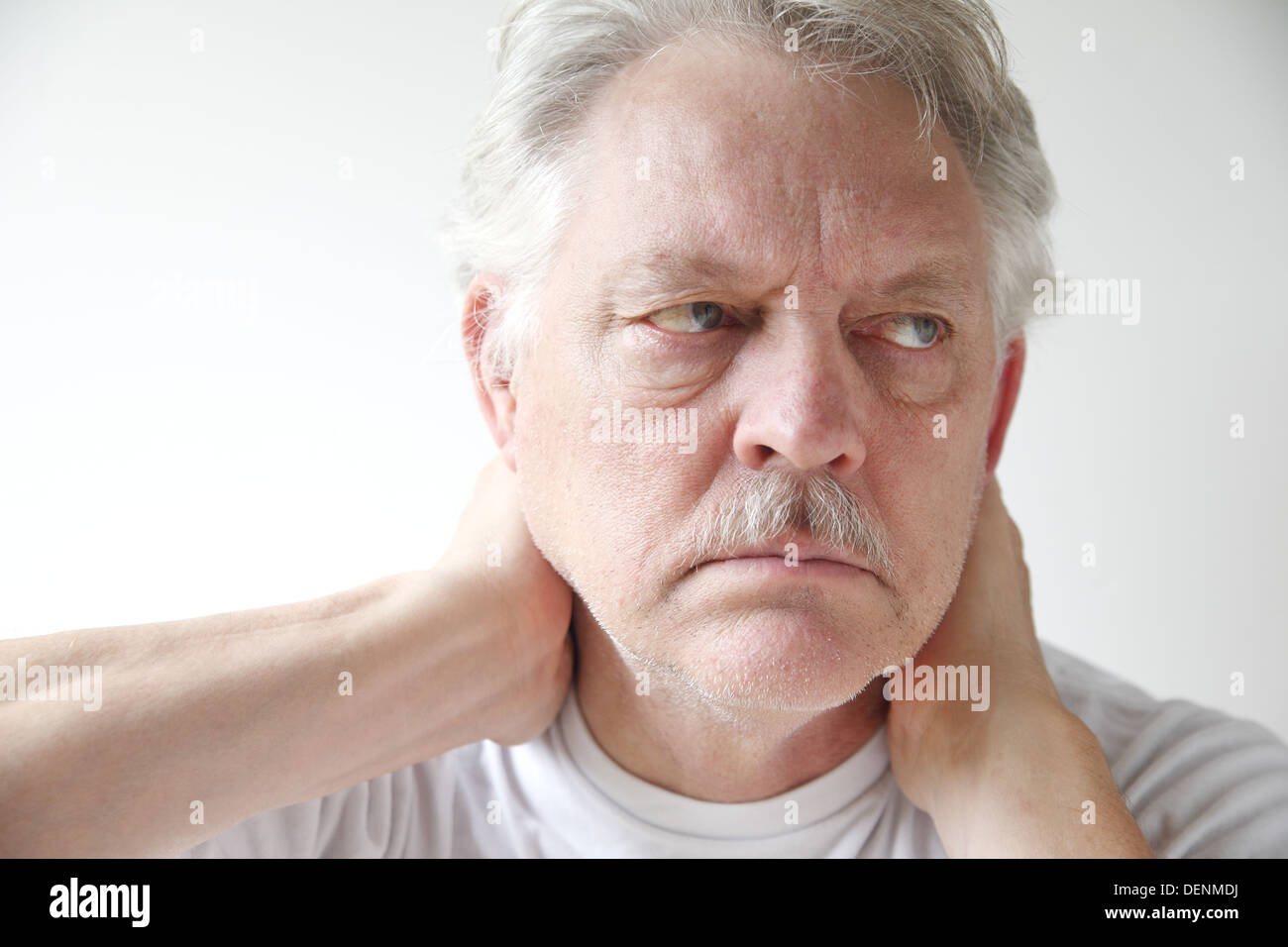 older man experiences soreness in his neck - Stock Image