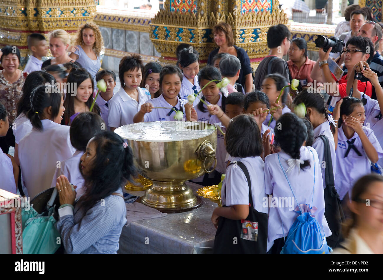Believers outside the Ubosoth. Wat Phra Kaew, or Temple of the Emerald Buddha. Grand Palace. Bangkok, Thailand, Asia. - Stock Image