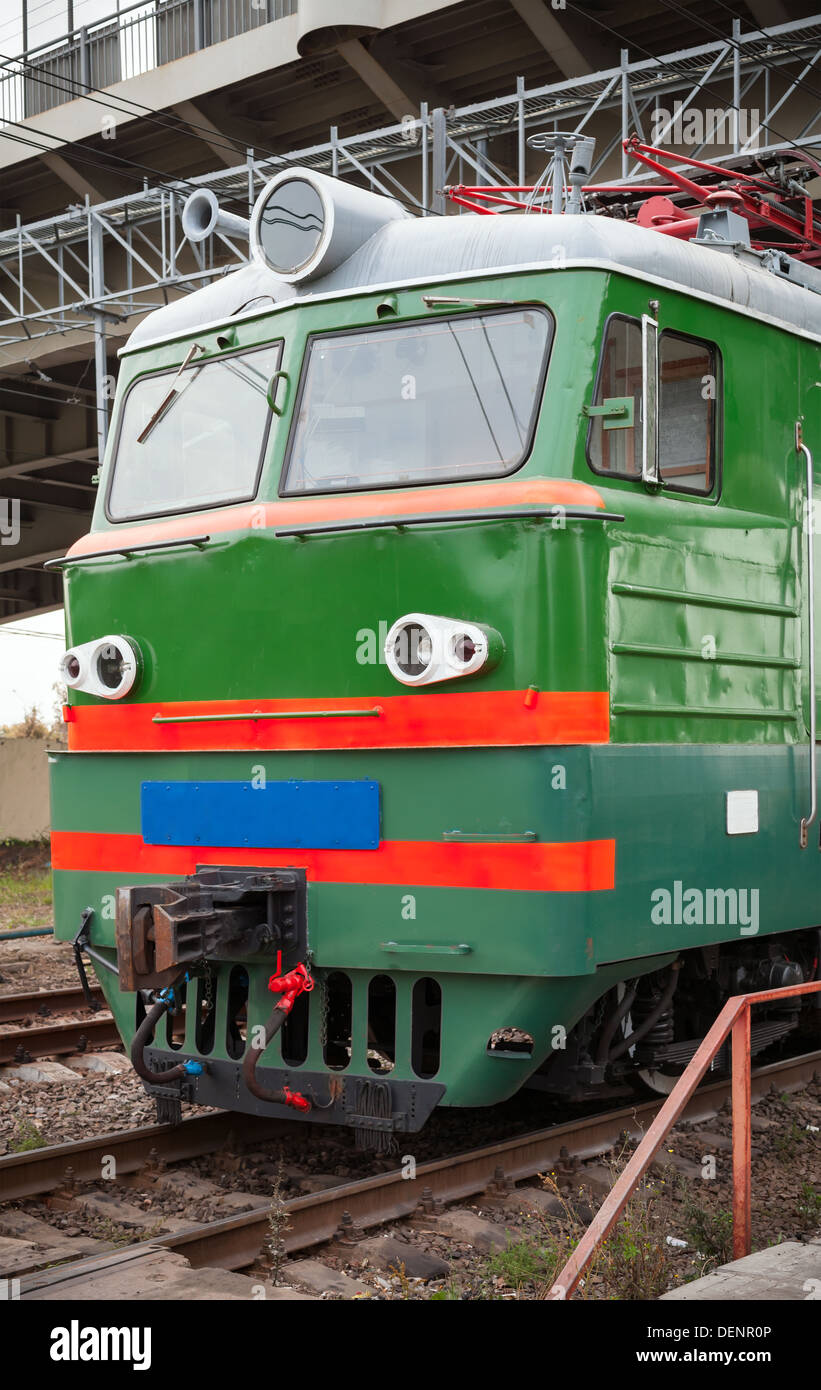Green locomotive with red stripes on the cabin stands on the railway station Stock Photo
