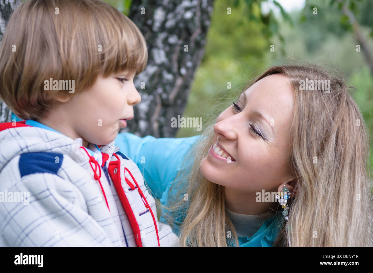 Happy family in the forest, focus on mother - Stock Image