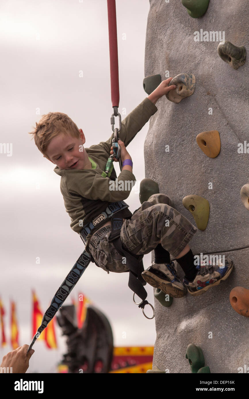 Boy on climbing wall in harness at Lindsay Fair and Exhibition in Kawartha Lakes - Stock Image