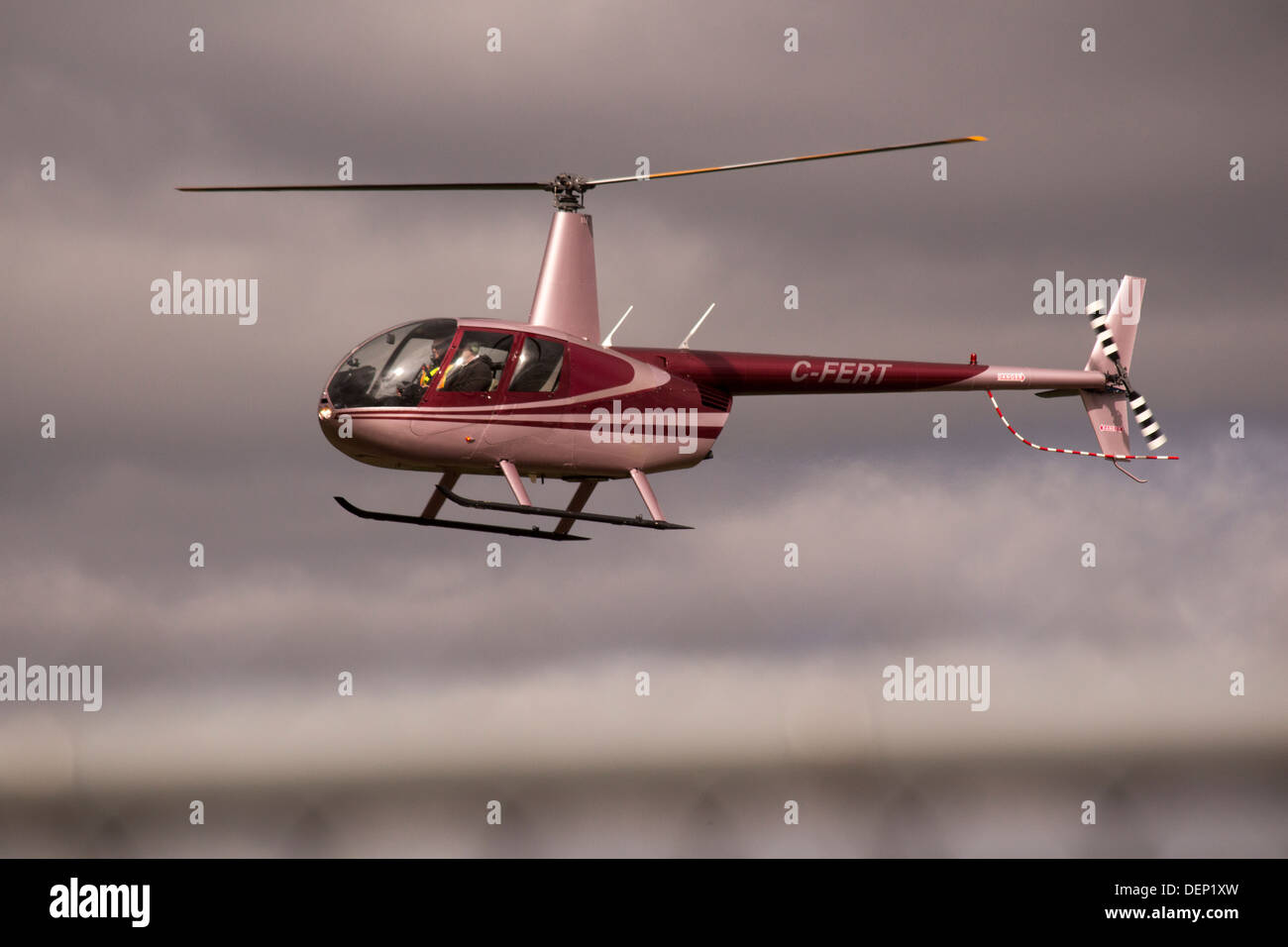 Red and White helicopter in sky flying passengers - Stock Image
