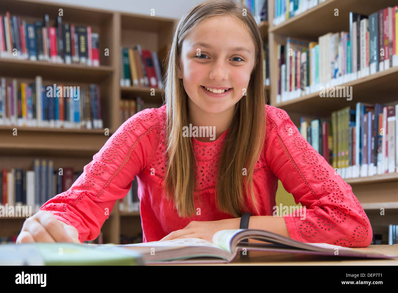 Caucasian student smiling in library Stock Photo