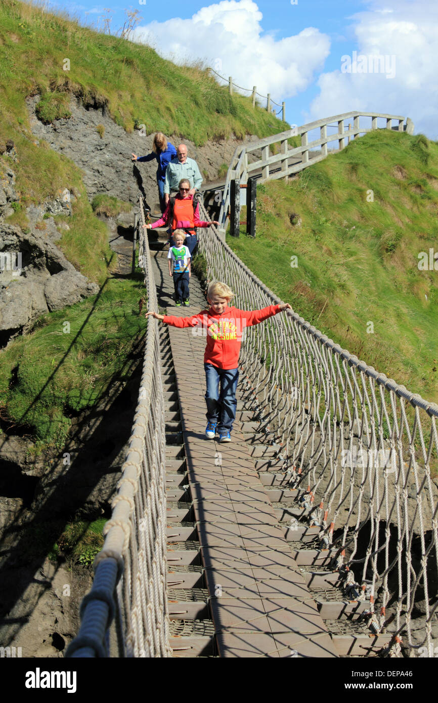 Family crossing Carrick-a-Rede, rope bridge on the Causeway Coastal Route, Northern Ireland. - Stock Image