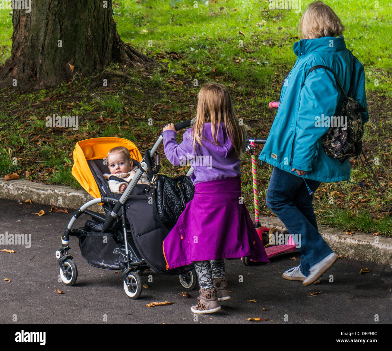 A family walking in the park, with a young child in buggy staring into the camera, Crystal Palace park, London England. - Stock Image