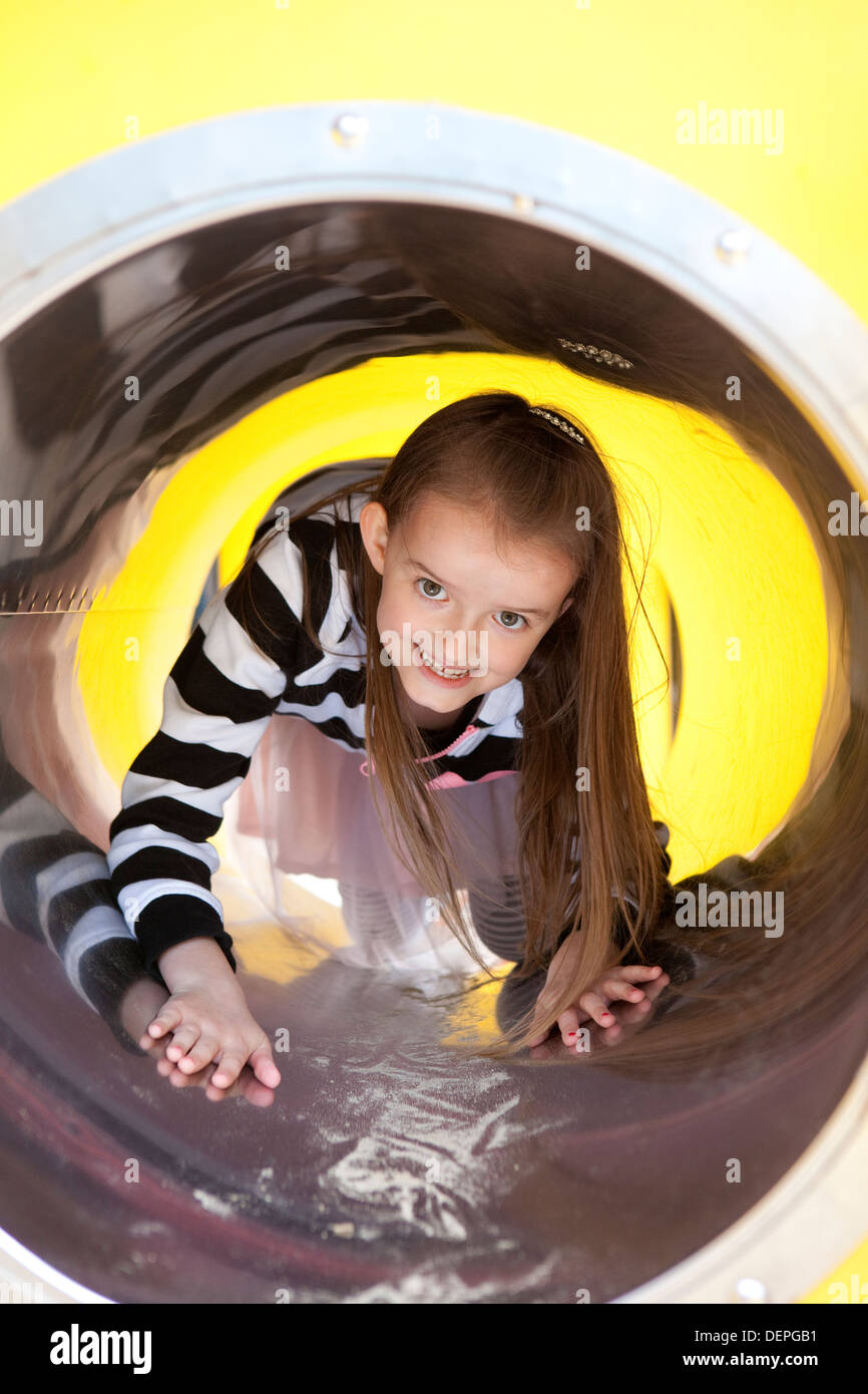 Young girl playing happily and crawling through a play tunnel at a playground. - Stock Image