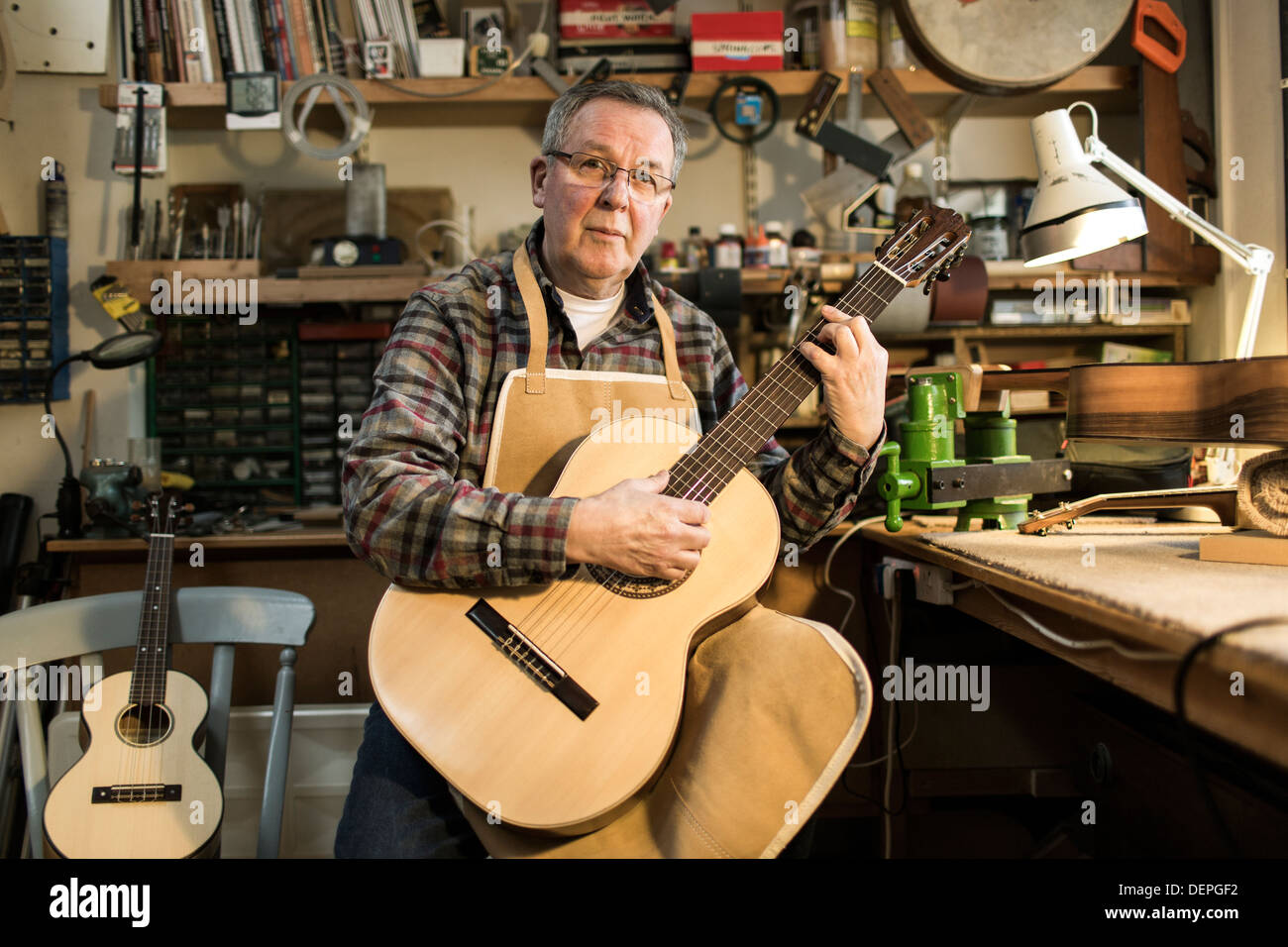 Guitar maker tuning and testing acoustic guitar in workshop, portrait - Stock Image