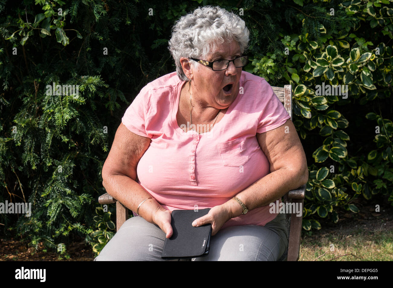 A shocked old / elderly / senior lady (aged 76) sitting in a chair in her garden. Stock Photo