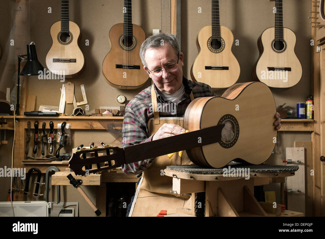 Guitar maker finishing acoustic guitar in workshop - Stock Image