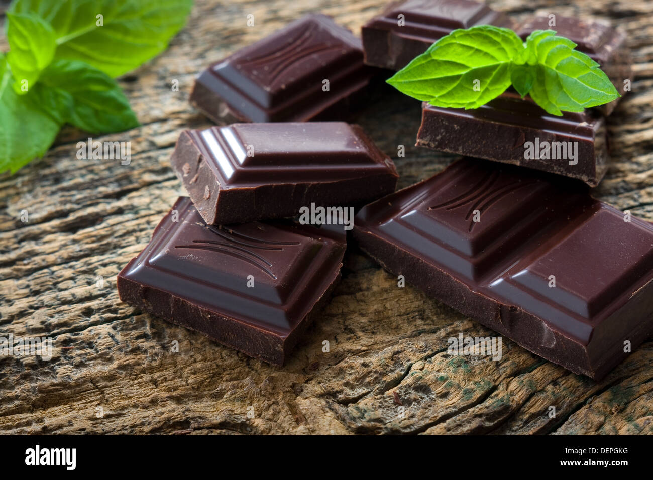 Dark chocolate pieces with a leaf of mint on wooden background - Stock Image