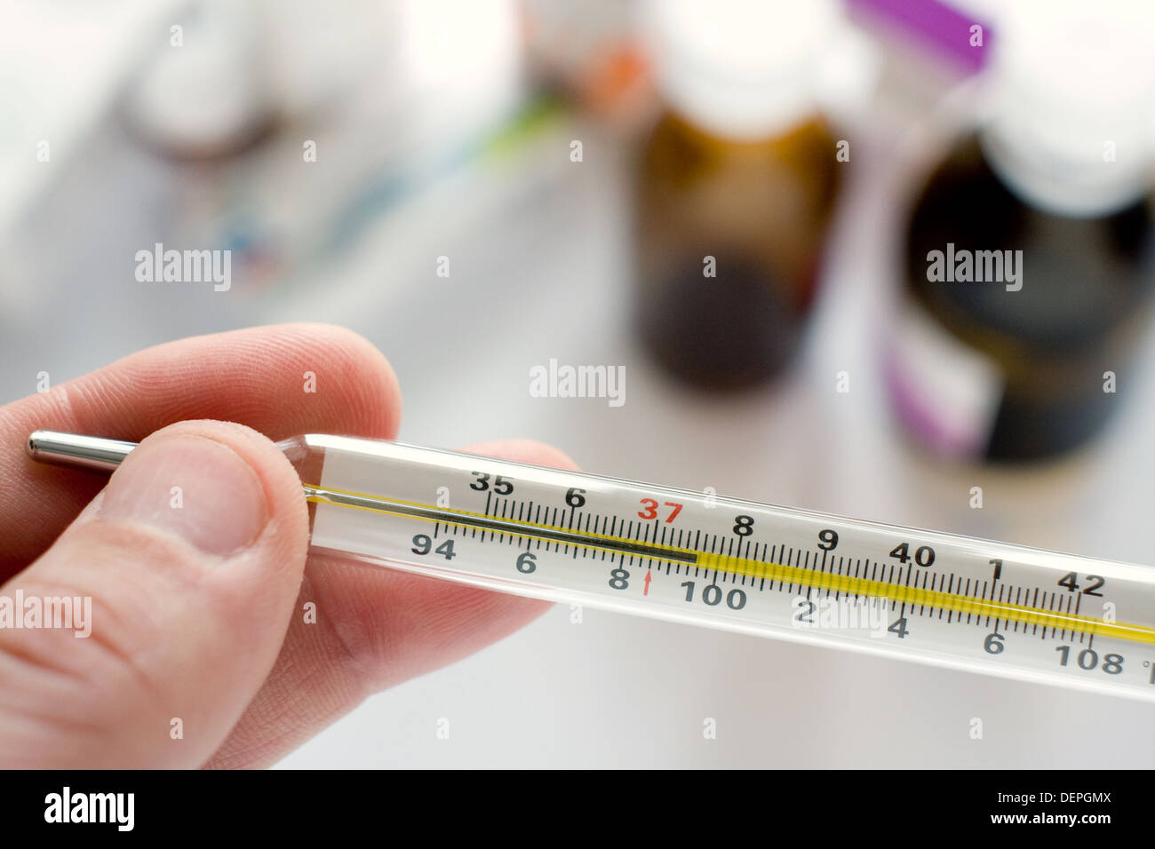 Doctor's hand holding thermometer indicating a high temperature - Stock Image