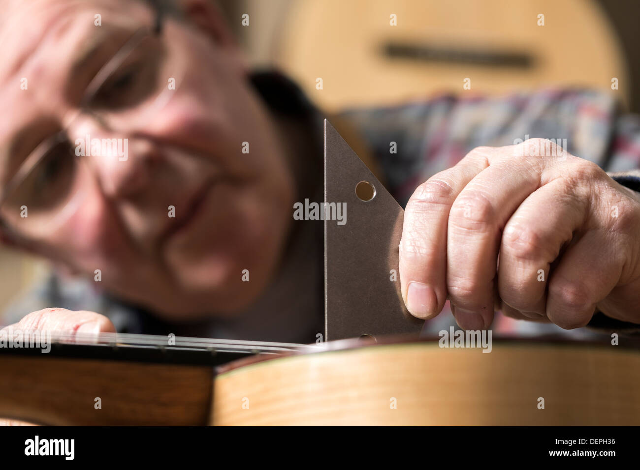 Close up of guitar maker finishing acoustic guitar in workshop - Stock Image