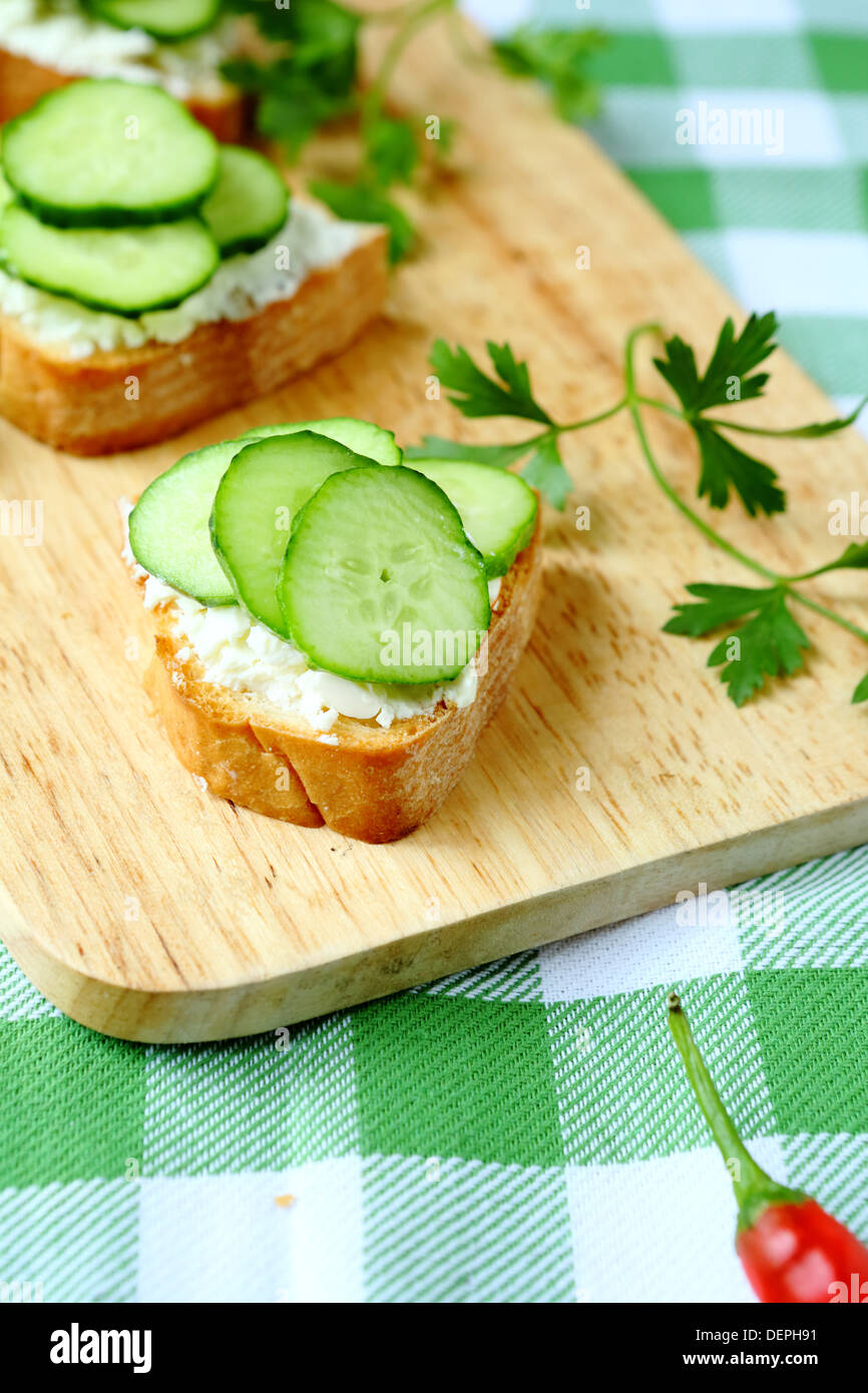 bruschetta with goat cheese and cucumber slices, food - Stock Image