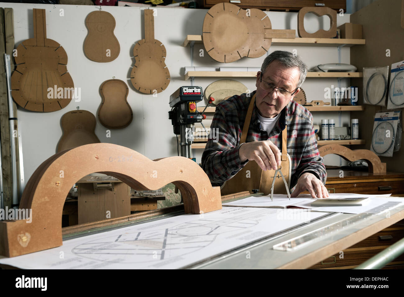 Guitar maker working on plans for an acoustic guitar in workshop - Stock Image