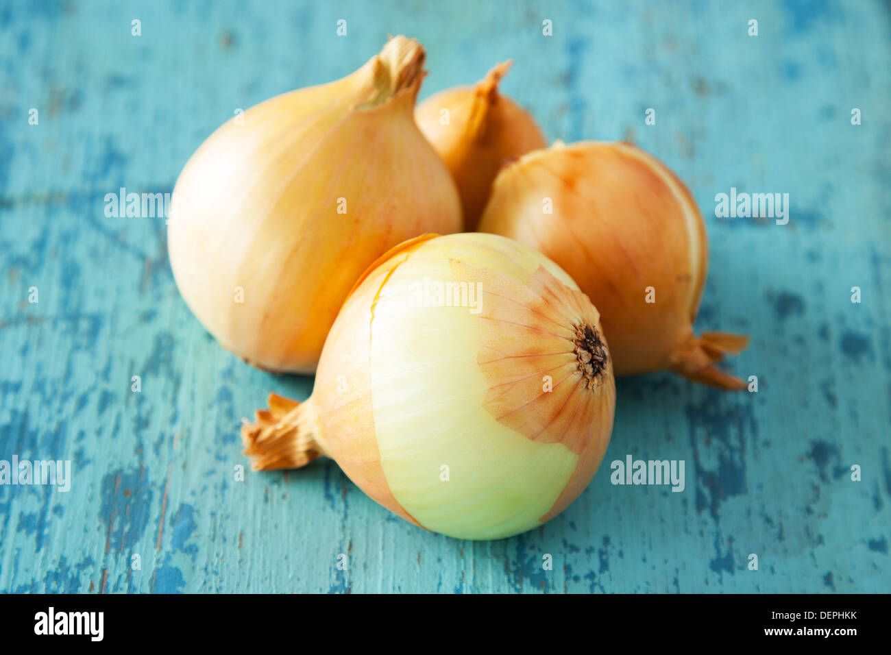 Onions on painted table. agriculture background - Stock Image