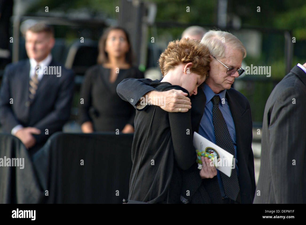 Family members and friends of victims hug following a memorial at the Marine Barracks to honor the victims of the Navy Yard shooting September 22, 2013 in Washington DC. - Stock Image