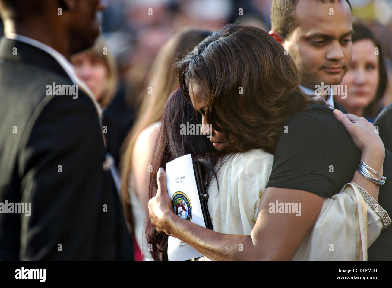 US First Lady Michelle Obama hugs family members during a memorial at the Marine Barracks to honor the victims of the Navy Yard shooting September 22, 2013 in Washington DC. - Stock Image