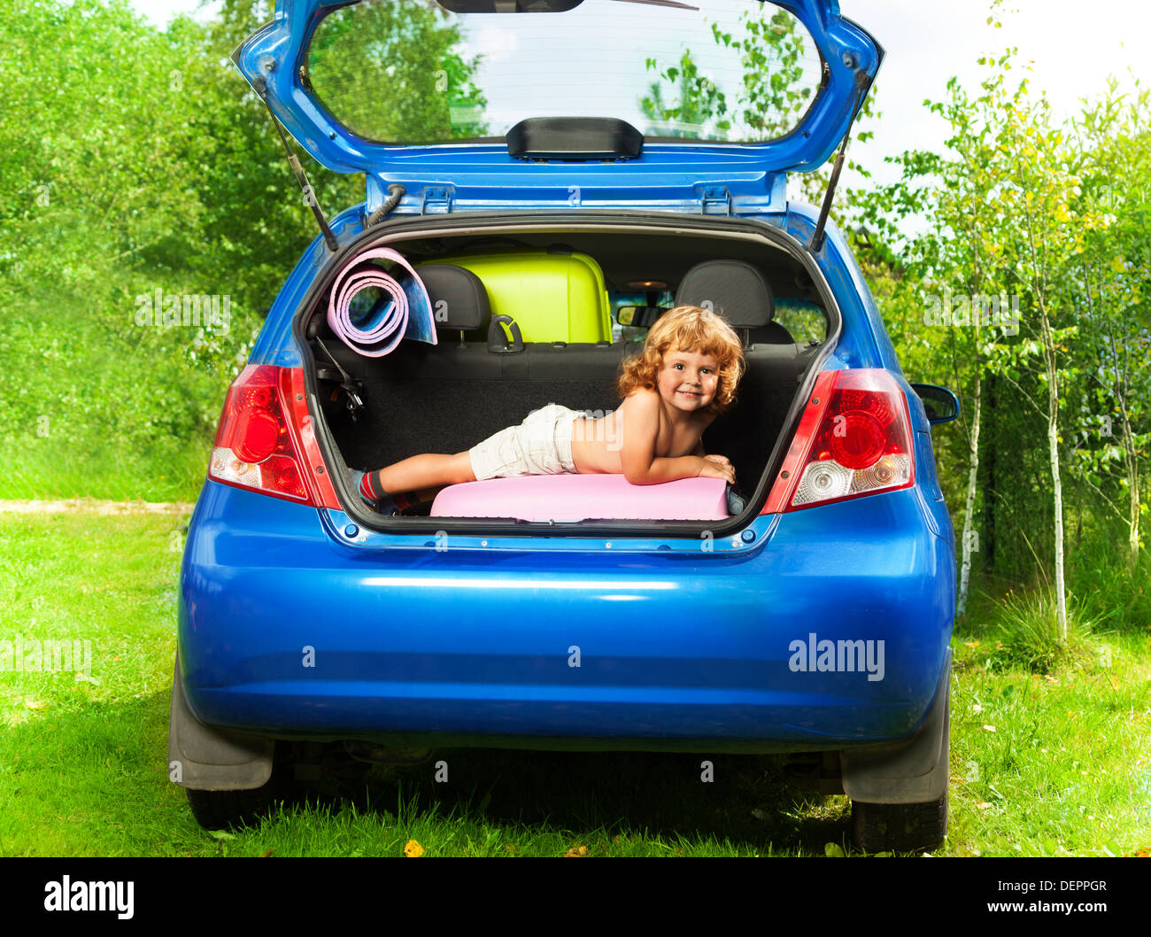 Cute little boy laying on the back of the bags and baggage in the car trunk ready to go on vacation - Stock Image