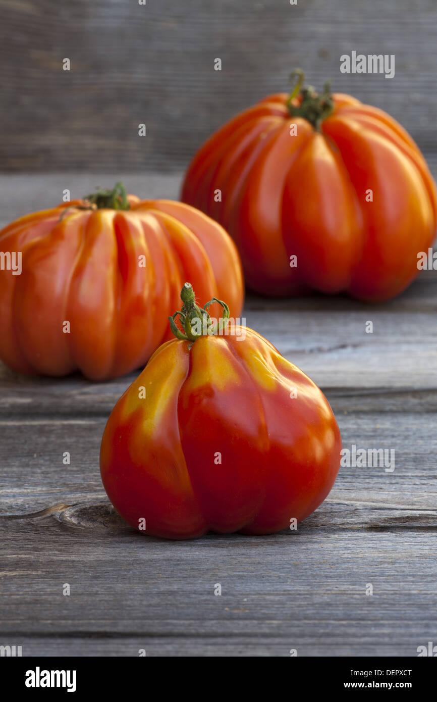 Three large Beefsteak Tomatoes fresh from the Weekly Market on a old wooden Table - Stock Image